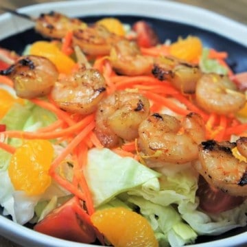 A bed of lettuce topped with tomato wedges, mandarin orange slices, shredded carrots and two grilled shrimp skewers, served in a blue bowl with a white rim