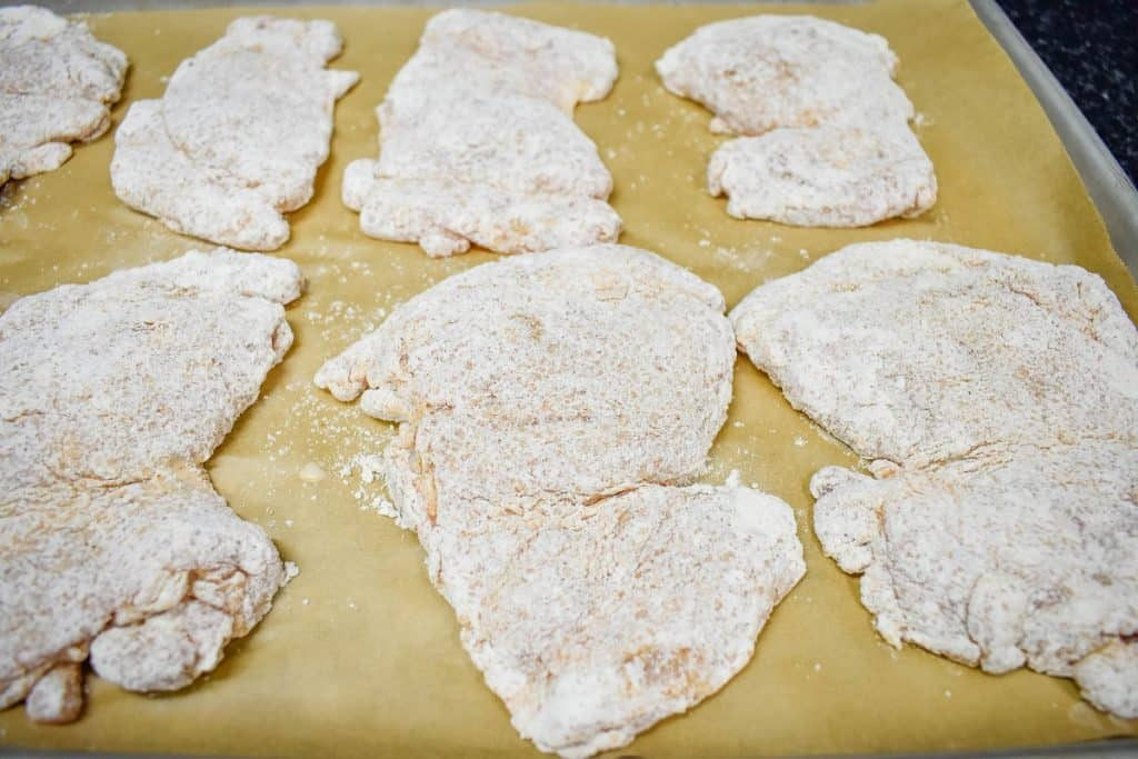 Chicken thighs coated in flour displayed on a baking sheet that's lined with brown parchment paper.
