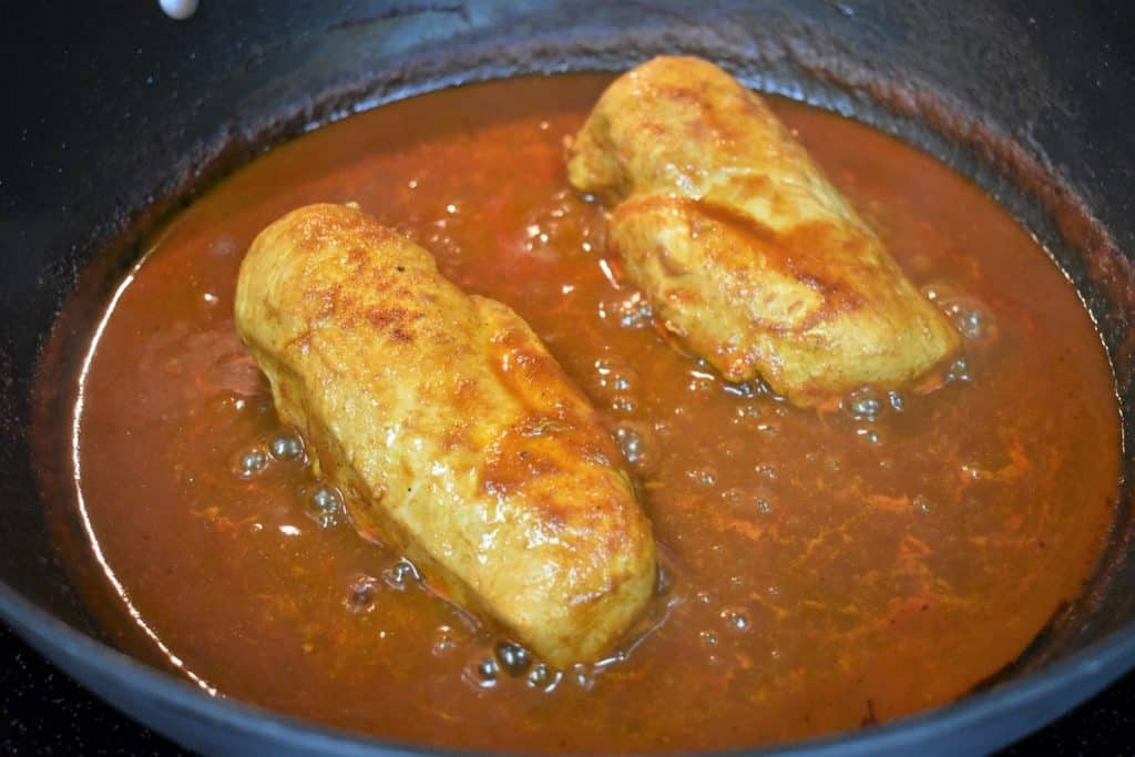 Two chicken breasts simmering in tomato sauce in a large black skillet.