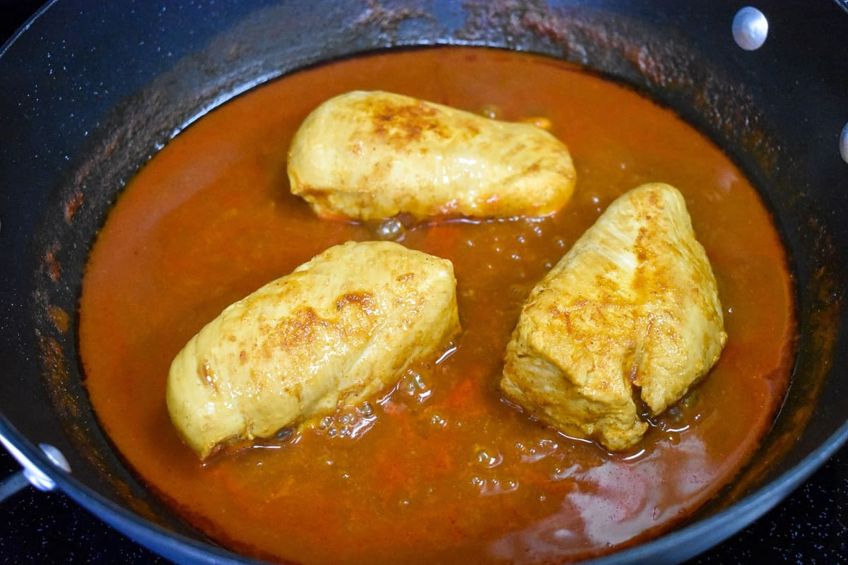 Three chicken breasts sitting in red sauce in a large, black skillet.