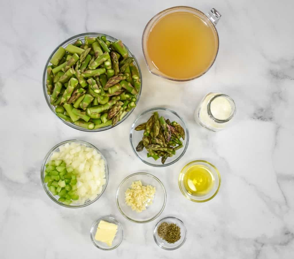 The ingredients for the cream of asparagus soup prepped and separated in glass bowls arranged on a white table.