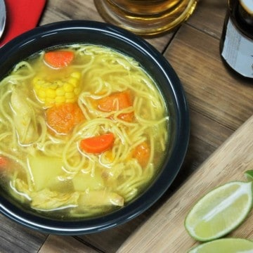 Cuban chicken soup with noodles carrots, potatoes, pumpkin, corn and chicken served in a dark gray bowl with lime wedges and a beer mug in the background.