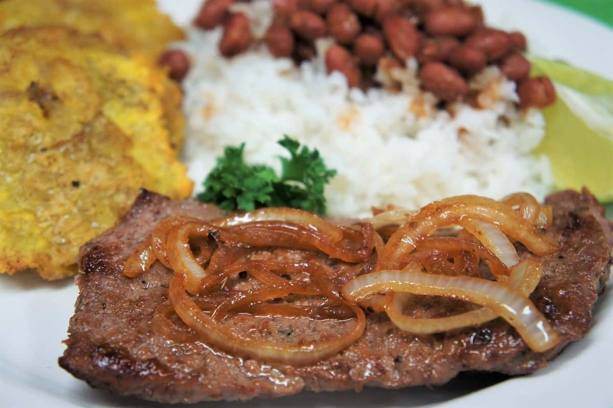 Cuban Cube Steak, topped with cooked onions and served with white rice, red beans and fried green plantains on the side.