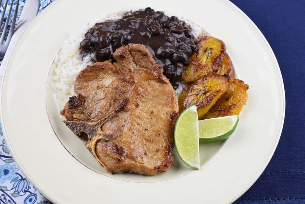 A thin cut, bone in pork chop served with white rice, black beans and fried sweet plantains on a white plate