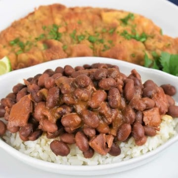 Cuban Style Red beans served over white rice with a breaded steak in the background