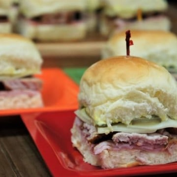 Cuban Sliders small sandwiches displayed on small colorful plates