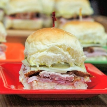 A close up of a cuban slider on a small red plate with other sliders in the background.