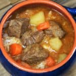 Cuban-Style Beef Soup a thick soup with beef, potatoes and carrots served in a blue crock.