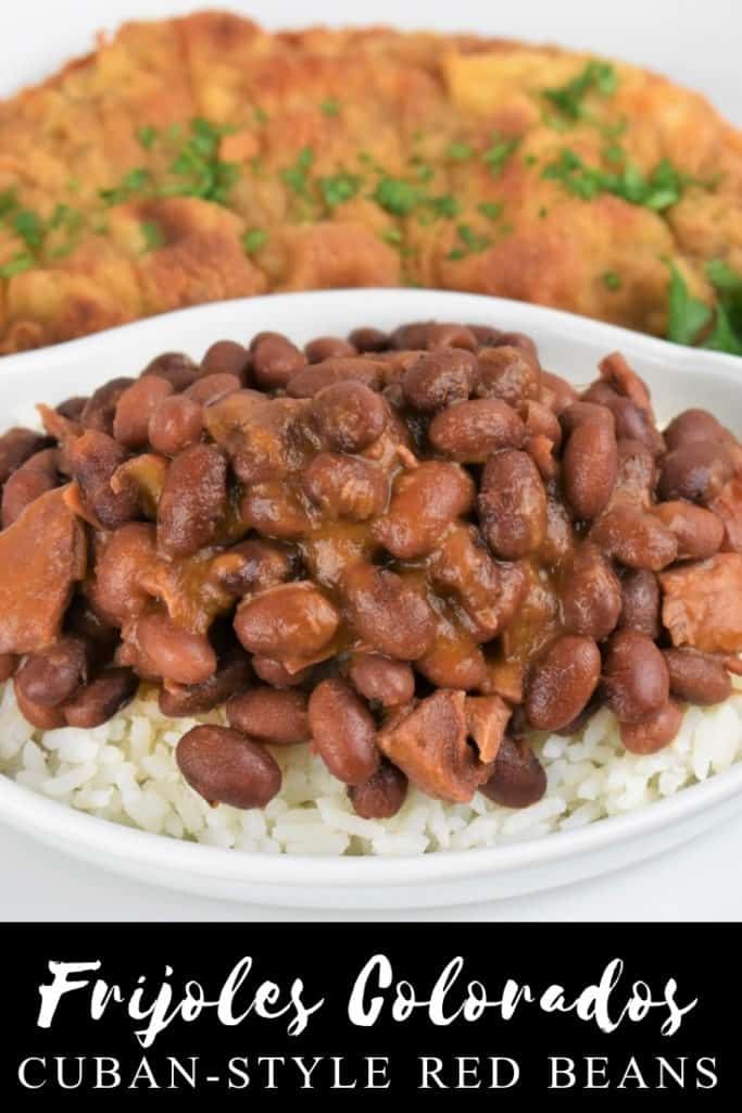 Cuban Style Red Beans served over white rice and a fried pork steak in the background.