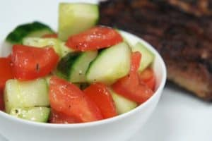 Cucumber Tomato Salad, diced and served in a small white bowl with ribs in the background
