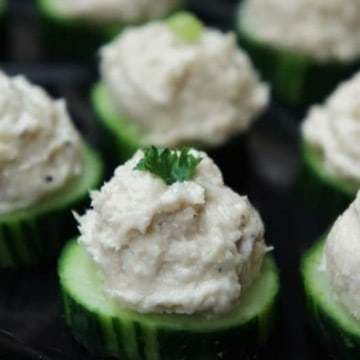 Cucumber Tuna Salad Bites thick cucumber slices topped with a small scoop of tuna salad arranged on a tray