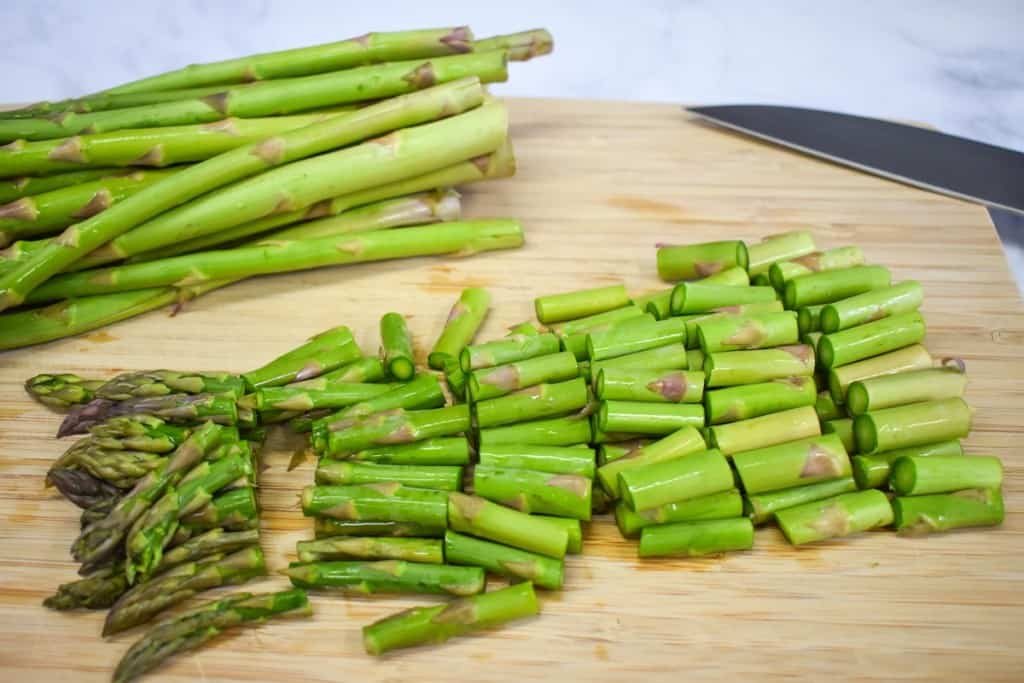 A bunch of asparagus spears cut into one inch pieces on a wood cutting board. The is an uncut bunch in the background.
