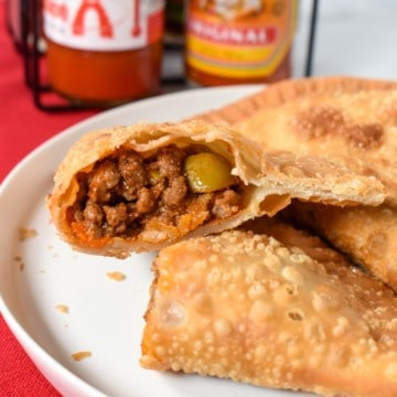 An image of an empanada cut in half so that the filling is exposed served on a white plate on a red linen with bottles of hot sauce in the background.