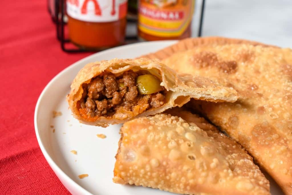 An picture of an empanada cut in half so that the filling is exposed served on a white plate on a red linen with bottles of hot sauce in the background.