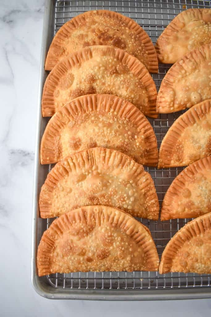 The fried empanadas set on a baking sheet lined with a cooling rack.