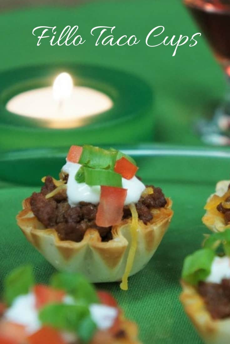 These festive little taco cups make a great appetizer. They're really easy to make too. The flaky and delicious fillo cups are filled with flavorful taco meat, then baked and topped with cheddar jack cheese. #tacocups #appetizers #partyfood #cocktailparty #holidayappetizers #fillocups #fillotacocups