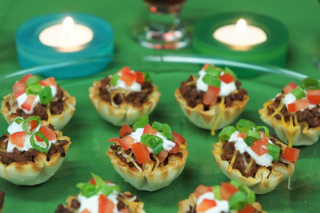 Fillo taco cups topped with sour cream, tomatoes and green onions arranged on a platter