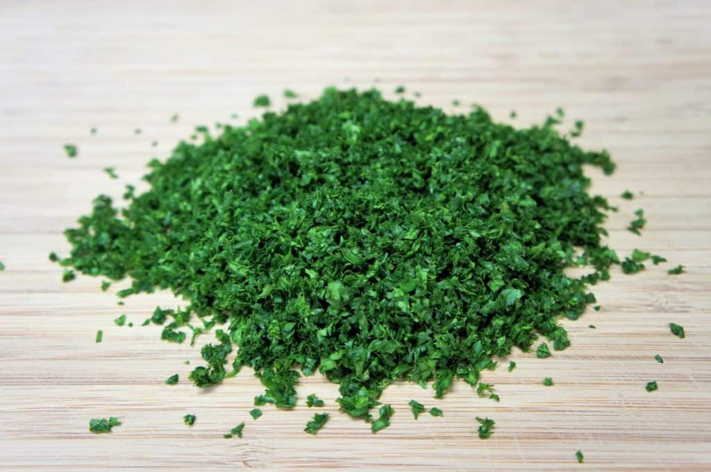 Finely chopped parsley on a wood cutting board