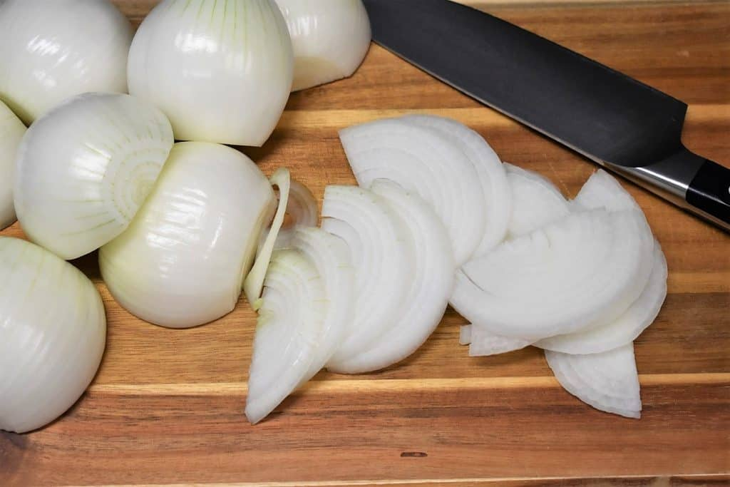 A sliced white onion on a wood cutting board with several peeled white onions in the background