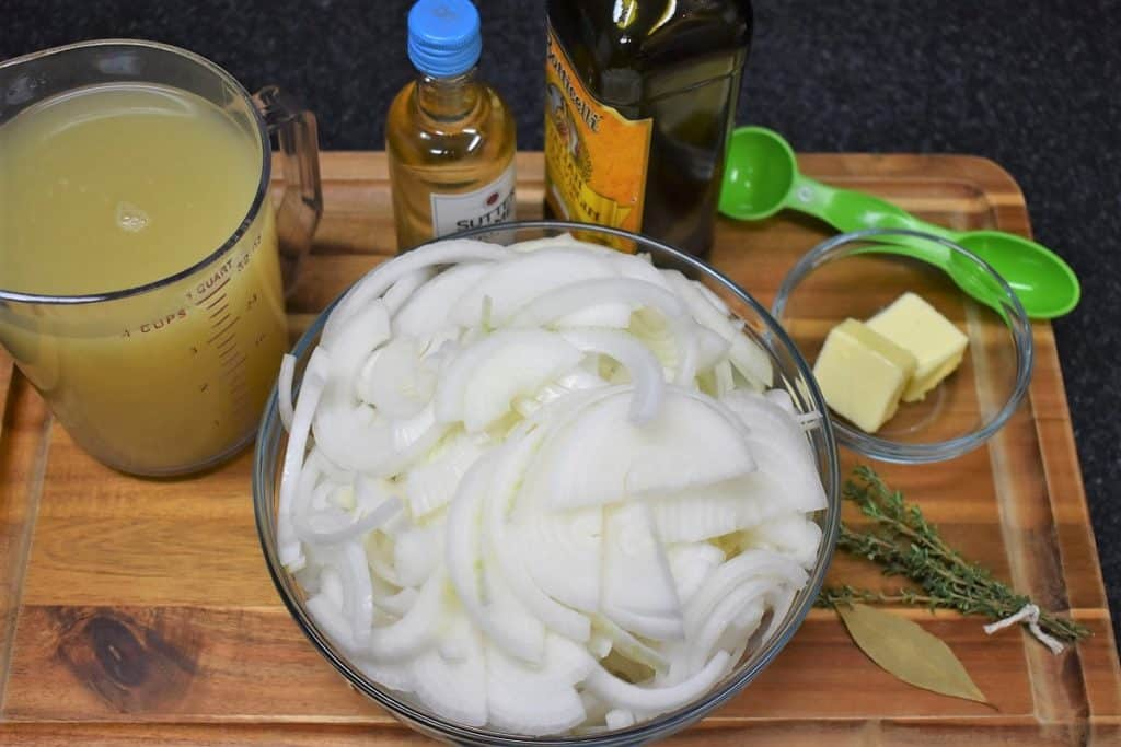 A large bowl of sliced white onions with chicken broth, small bottle of white wine, olive oil and butter arranged on a wood cutting board