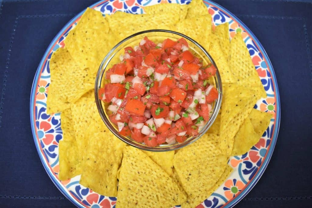 Fresh salsa in a clear bowl served with corn tortilla chips.