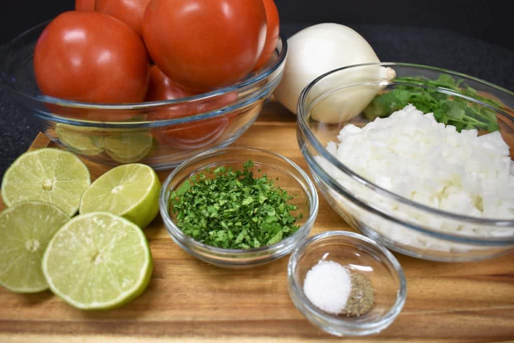 Fresh salsa ingredients, tomatoes, onions, cilantro, limes, salt and pepper on a wood cutting board.
