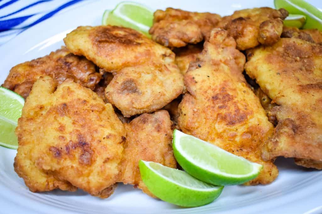 Fried chicken thighs arranged on a large white platter and served with lime wedges.