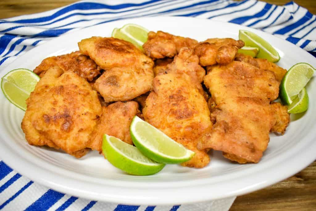 Fried chicken thighs arranged on a large white platter on a blue and white striped cloth and garnished with lime wedges.