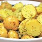 Gold potatoes, cut in half and tossed in a minced garlic and dill oil, served in a white rimmed blue bowl.