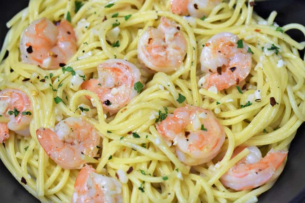 A close up picture of spaghetti topped with shrimp in a garlic oil and garnished with parsley.