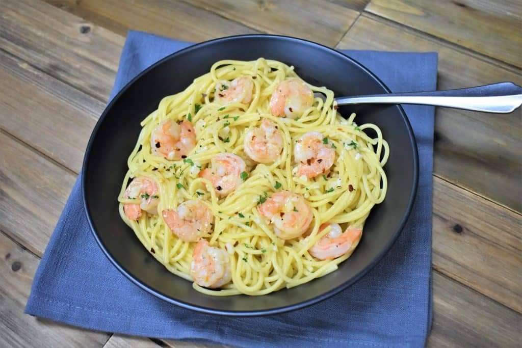 Spaghetti topped with shrimp in an oil and garlic sauce, garnished with parsley and served in a large black bowl.