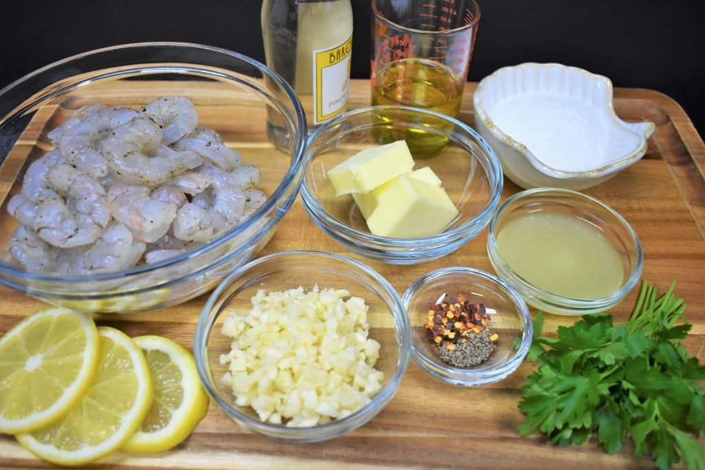 The ingredients for the garlic shrimp pasta recipe displayed on a wood cutting board.