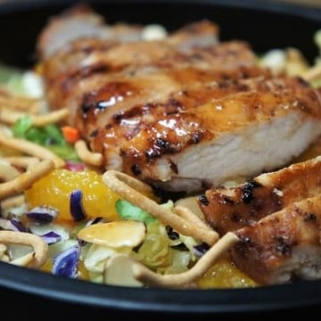 Grilled Chicken Asian Salad, lettuce served in a black bowl topped with grilled, sliced chicken breast, mandarin orange slices, chow mein noodles and sliced almonds