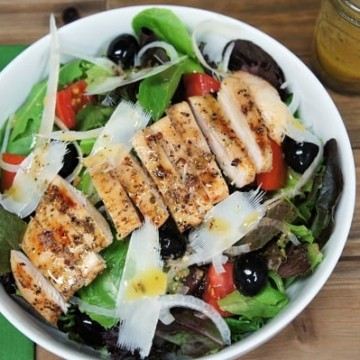 Grilled Chicken Italian Salad, a bed of lettuce served in a large white bowl and topped with sliced chicken breast, tomato wedges, black olives, thinly sliced onions and shavings of Parmesan cheese