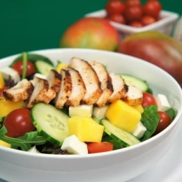 Grilled Chicken Mango Salad, a bed of mix spring lettuce, topped with sliced cucumbers, grape tomatoes, sliced grilled chicken and cubes of mozzarella and mango