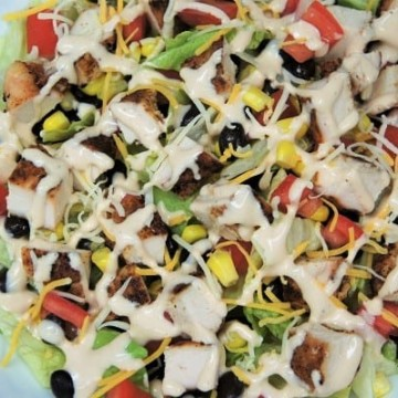 Grilled Chicken Southwestern Salad, a chopped salad loaded with chicken, corn, black beans tomatoes and covered in a drizzle of dressing