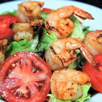 Grilled Shrimp Salad, a bed of lettuce topped with sliced tomatoes and topped with large grilled shrimp