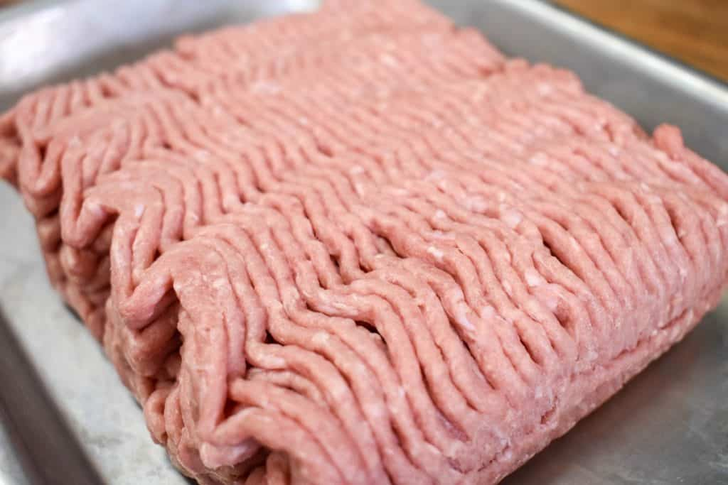 Uncooked ground turkey right out of the package on a small metal sheet pan.