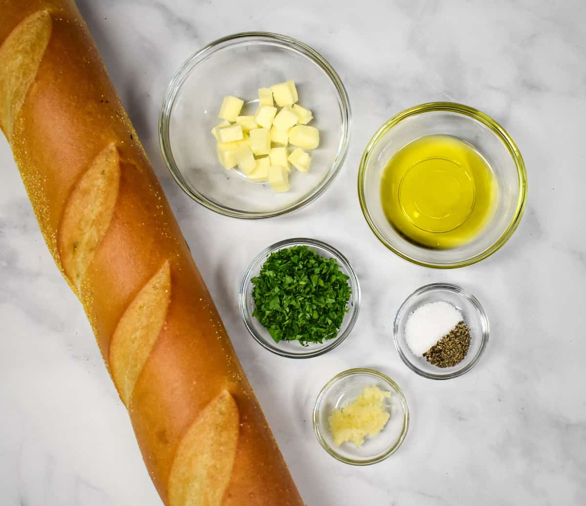 The ingredients for the garlic bread prepped and arranged in glass bowls on a white table with a whole loaf of bread on the left side.