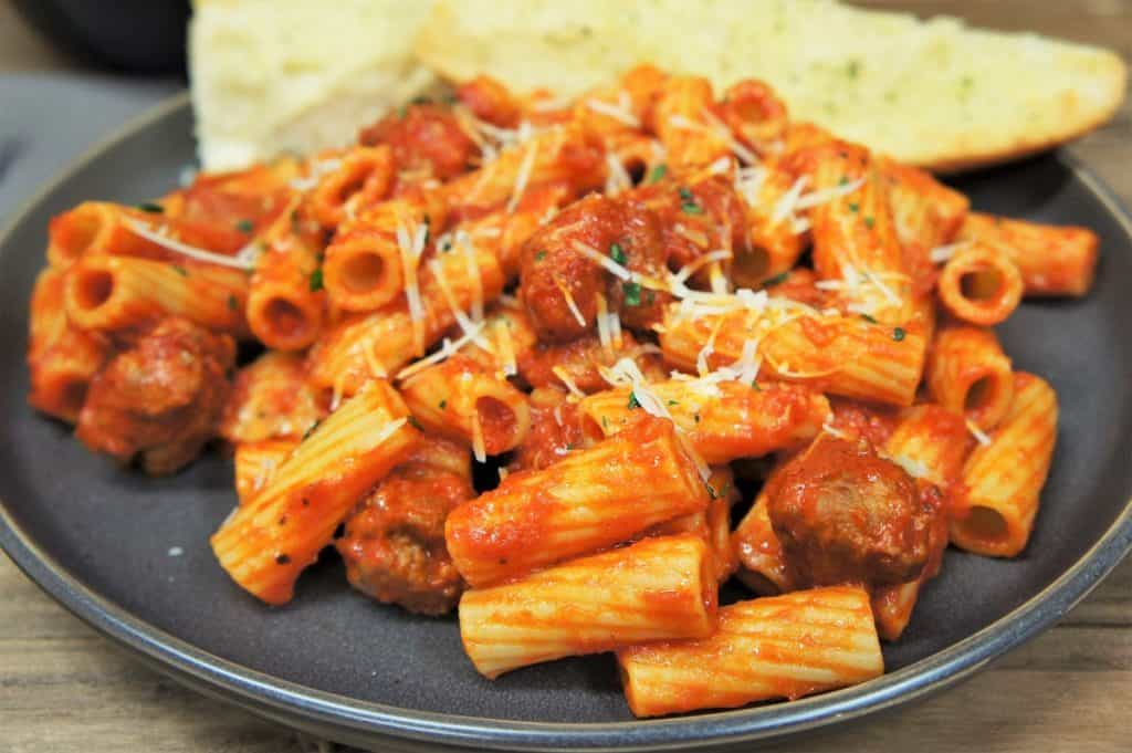 Rigatoni pasta tossed with Italian sausage pasta sauce served on a gray plate with garlic bread in the background.