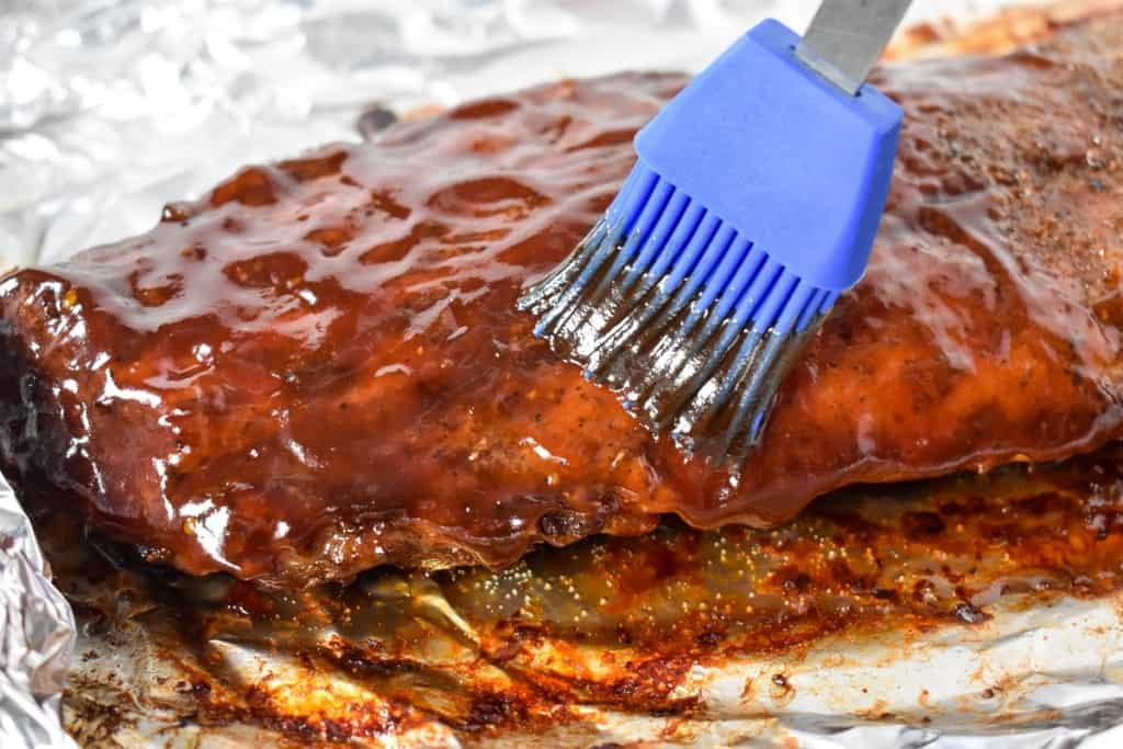 An image of the cooked ribs being brushed with the barbecue sauce with a blue brush.
