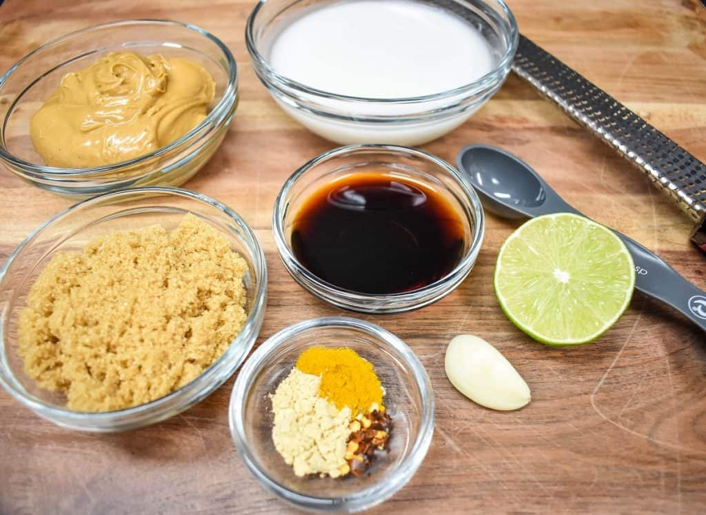 The ingredients for the peanut sauce in clear, glass bowls displayed on a wood cutting board.