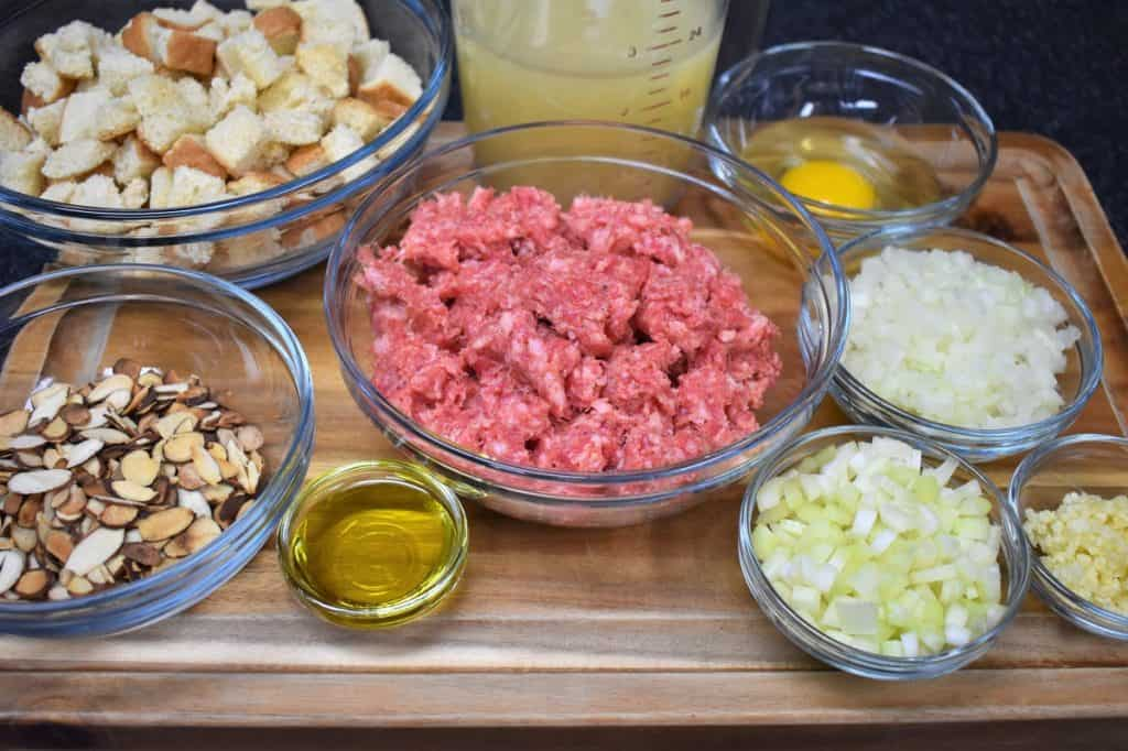 Ingredients for Sausage Stuffing arranged on a wood cutting board