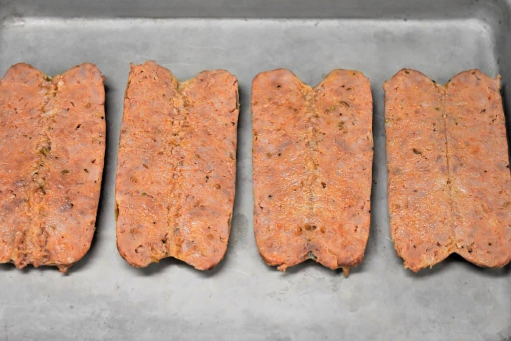 Four Italian Sausages butterflied on a metal baking sheet