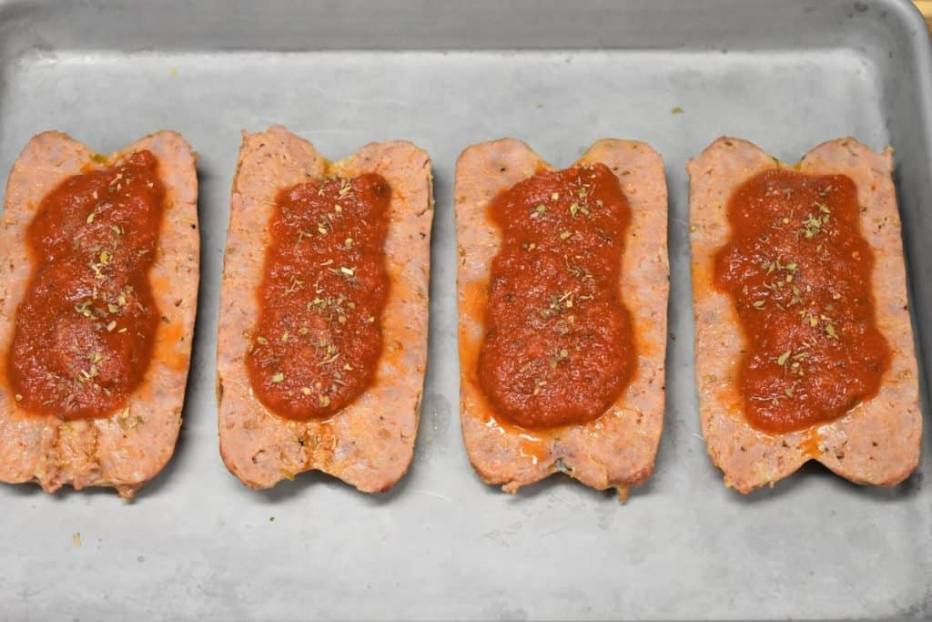 Four butterflied Italian sausages butterflied on a metal baking sheet and topped with tomato sauce and a sprinkle of oregano and garlic powder