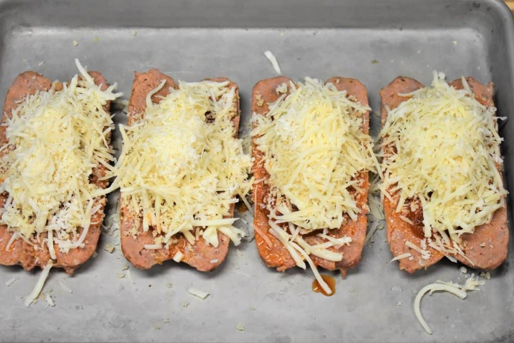 Italian Sausage Parmigiana unbaked on a metal baking topped with tomato sauce, cheese and breadcrumbs