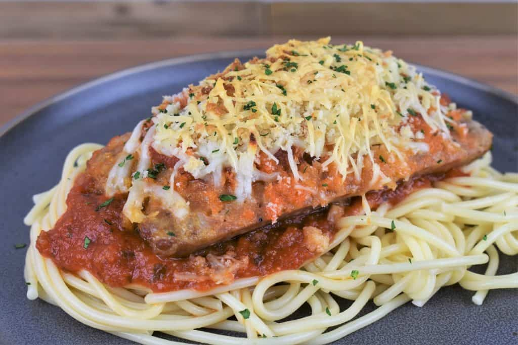 Italian Sausage Parmigiana on a generous bed of spaghetti topped with red sauce served on a gray plate.