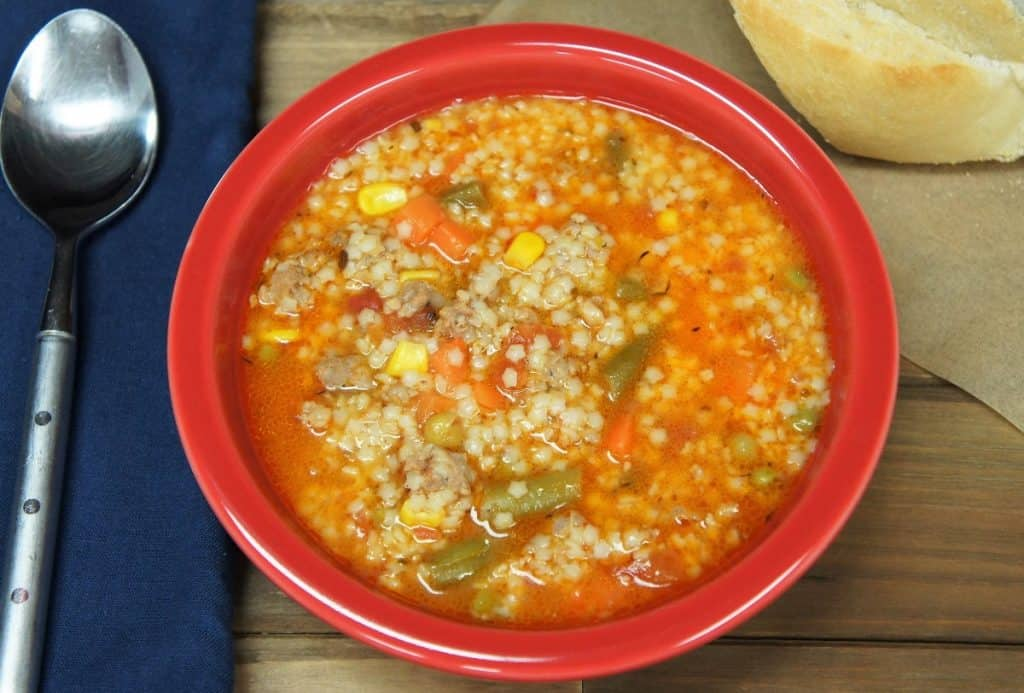 Italian sausage and pastina soup served in a red bowl with a piece of bread in the background and a large spoon and blue napkin to the left.