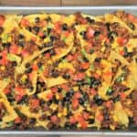 Loaded Sheet Pan Nachos topped with ground turkey, melted cheese, black beans, corn and diced tomatoes