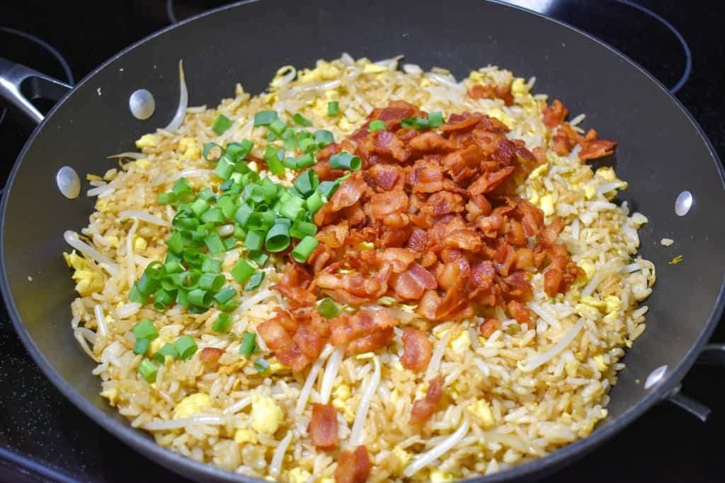 The cooked bacon and green onions on top of the fried rice mixture in a large, black skillet.